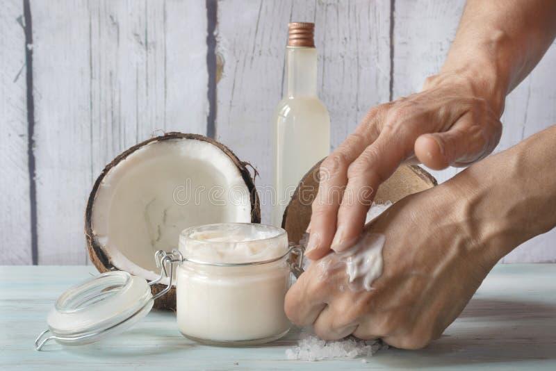 Menselijke handen die eigengemaakte kokosnoot en rozenroom smeren stock afbeelding