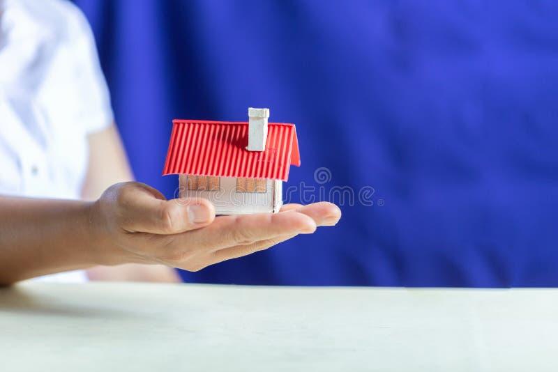 Menselijke handen die model van droomhuis houden royalty-vrije stock afbeelding