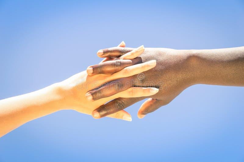 Menselijke handen die tussen verschillende rassen vingers voor vriendschap en liefde kruisen royalty-vrije stock foto