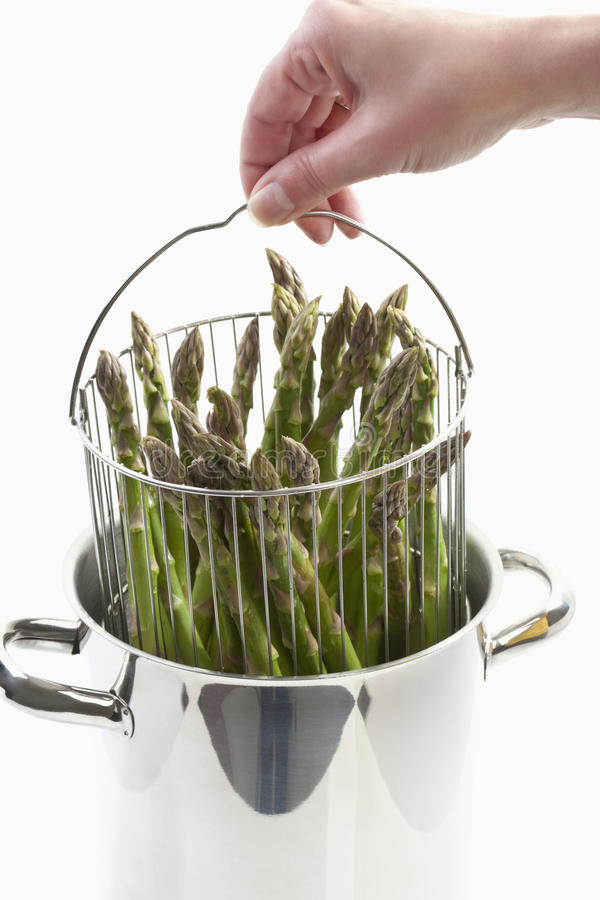 Menselijke holdings kokende pot met groene asperge royalty-vrije stock foto's