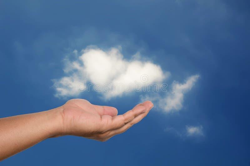 Menselijke open hand met witte wolk op blauwe hemel royalty-vrije stock afbeeldingen