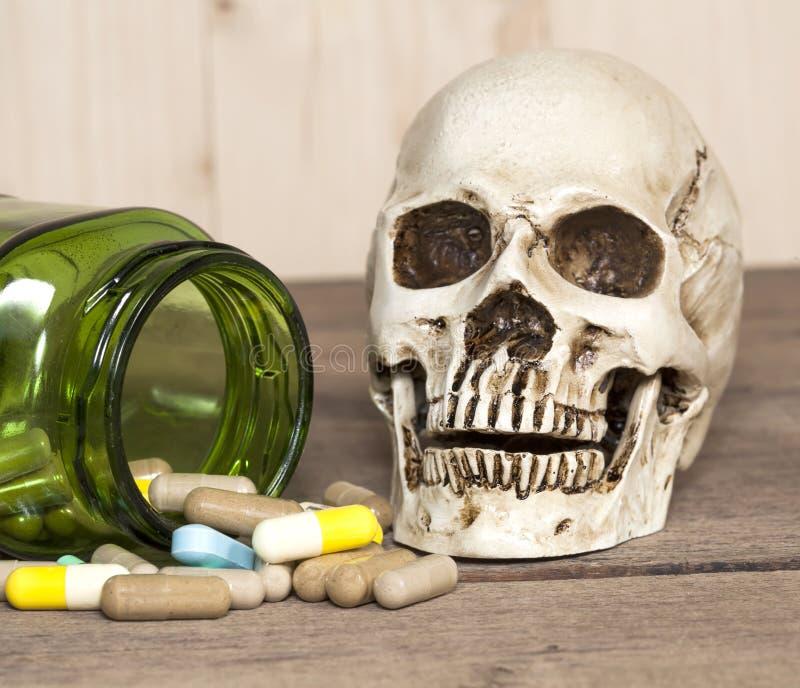 Menselijke schedel met drugs op hout stock afbeelding
