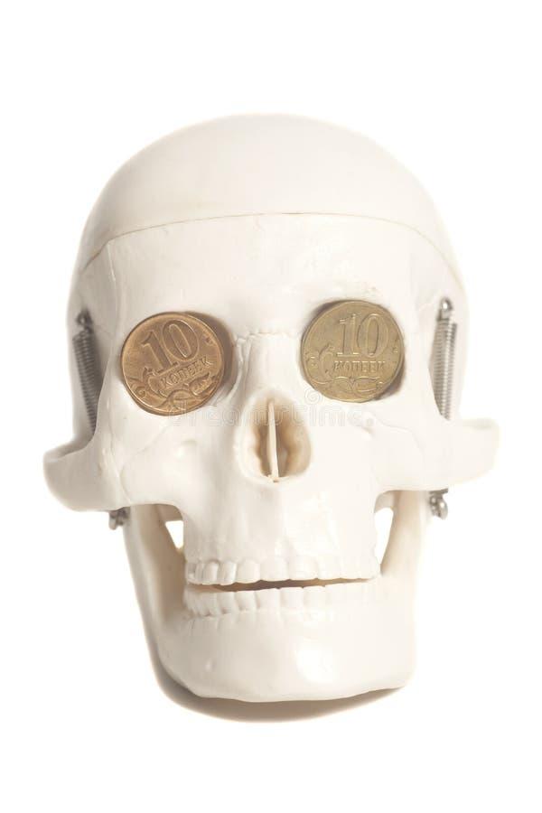 Menselijke schedel met geldmuntstukken stock fotografie