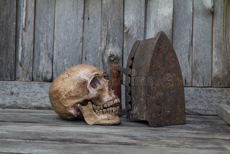 Menselijke schedel op de vloer met oud houten oud fornuis, Stilleven royalty-vrije stock afbeeldingen
