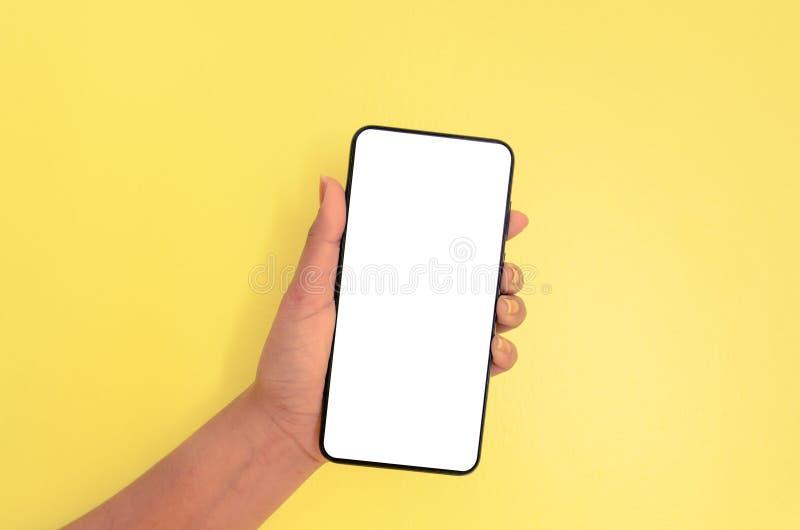 Menselijke smartphone van de handholding met witte het schermachtergrond stock afbeeldingen