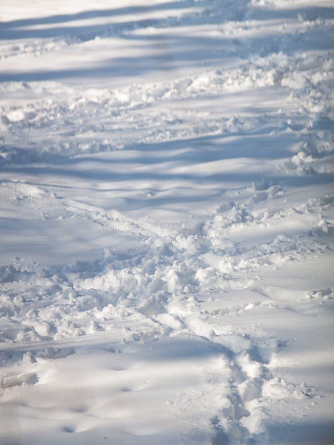 Menselijke voetafdrukken op de blauwe sneeuw royalty-vrije stock foto's