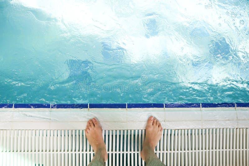 Menselijke voeten op de rand van de pool royalty-vrije stock afbeelding