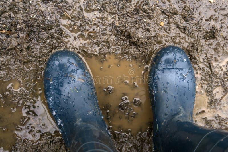 Menselijke voeten in rubberlaarzentribune in de modder royalty-vrije stock afbeeldingen