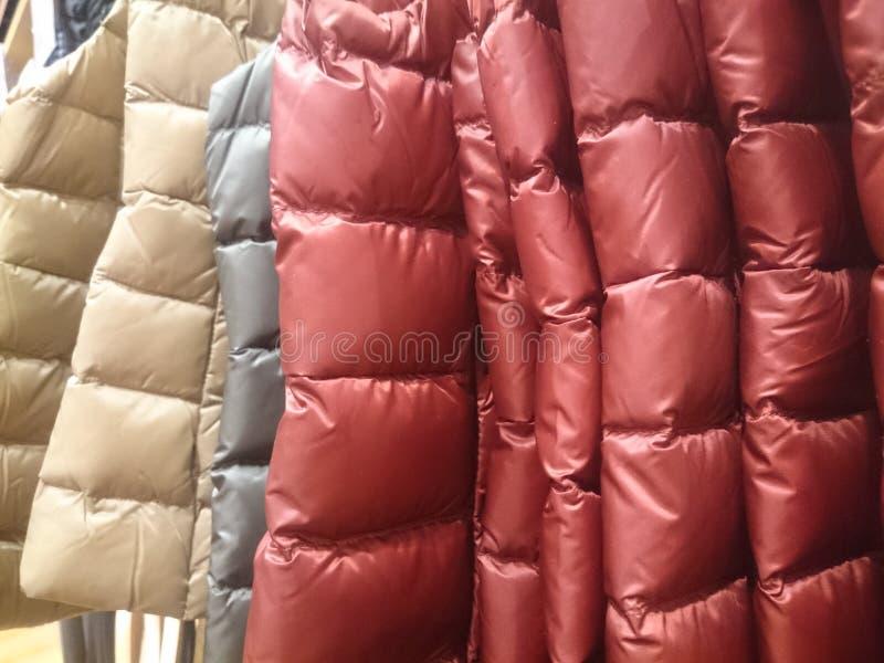 Mensen 'sdown jasjes en vesten op opslagplanken royalty-vrije stock afbeeldingen