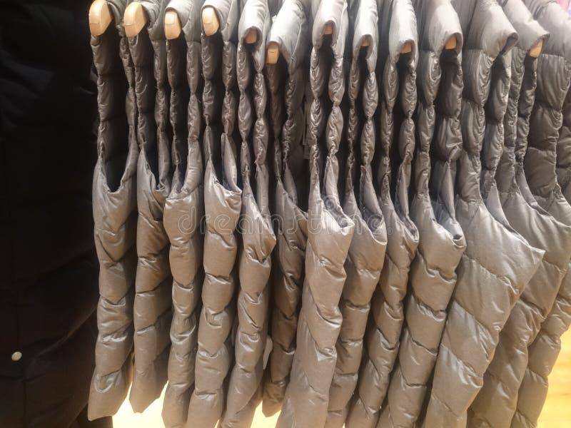 Mensen 'sdown jasjes en vesten op opslagplanken stock foto