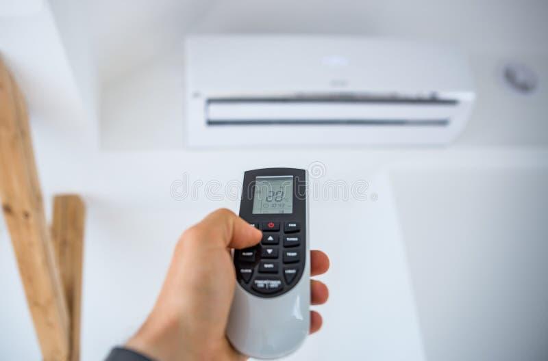 Mensen aanpassende en regelende temperatuur op huisairconditioner stock fotografie