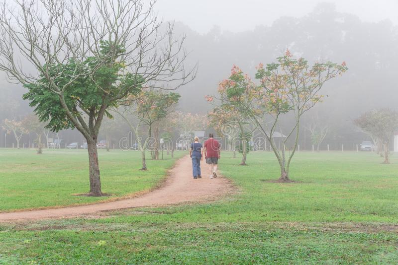 Mensen aanstoten, die bij stedelijk park in mistige dalingsochtend uitoefenen royalty-vrije stock afbeeldingen