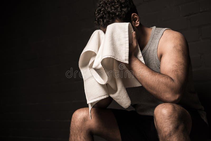 Mensen afvegend gezicht door handdoek bij gymnastiekkleedkamer stock foto's