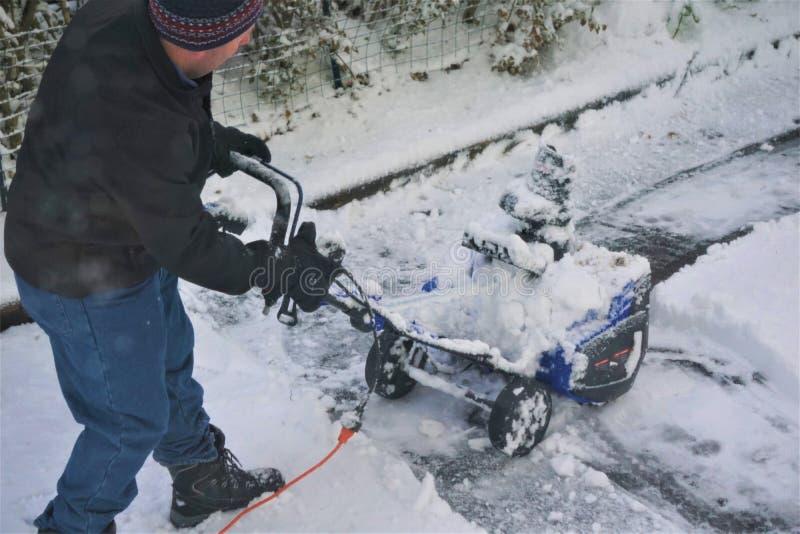 Mensen beginnende sneeuwblazer op oprijlaan royalty-vrije stock foto's