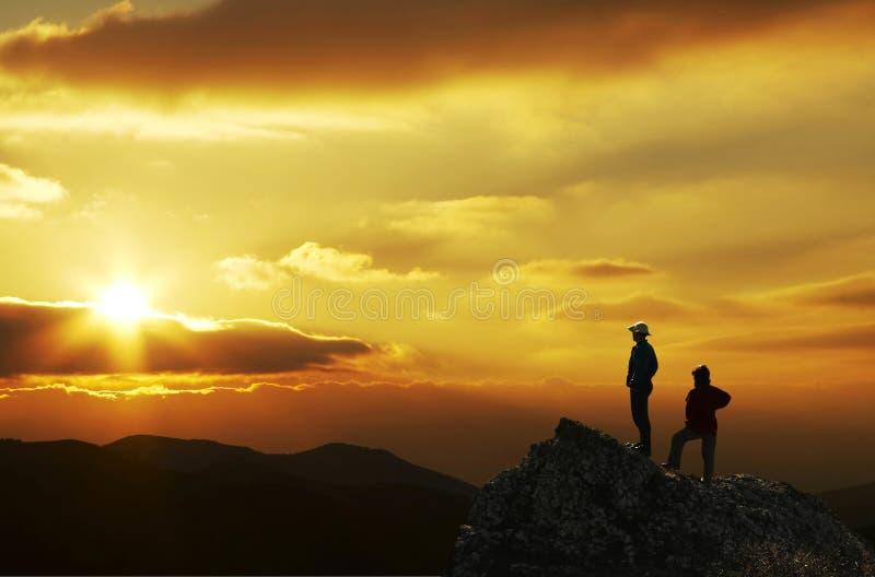 Mensen in berg op zonsondergang royalty-vrije stock afbeeldingen