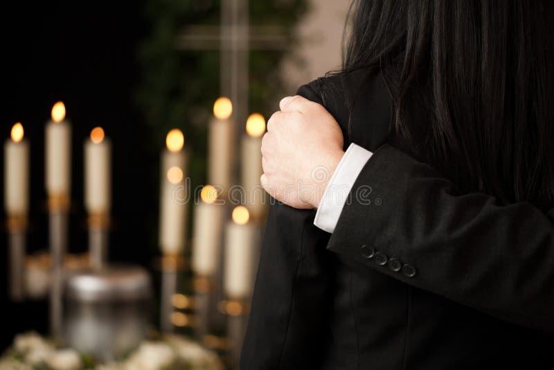 Mensen bij begrafenis die elkaar troost stock foto