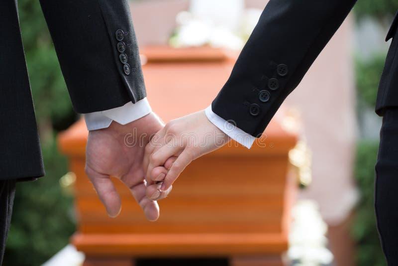 Mensen bij begrafenis die elkaar troosten stock afbeelding
