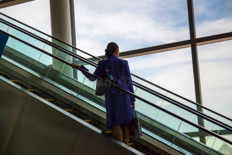 Mensen bij de luchthavenroltrap De luchthavenroltrap dat mening door het glas aan de buitenkant heeft stock afbeelding