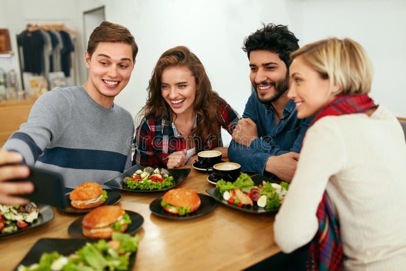 Mensen bij Diner die Foto's op Telefoon nemen Vrienden het Video Roepen stock fotografie