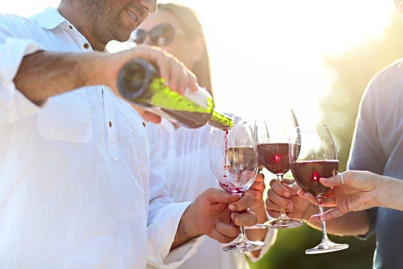 Mensen bij wijn openluchtpartij stock afbeeldingen