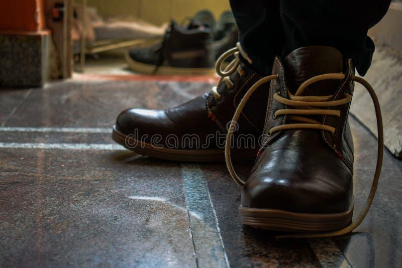 Mensen bruine laarzen met bruin kant die voor het perfecte beeld stellen royalty-vrije stock foto