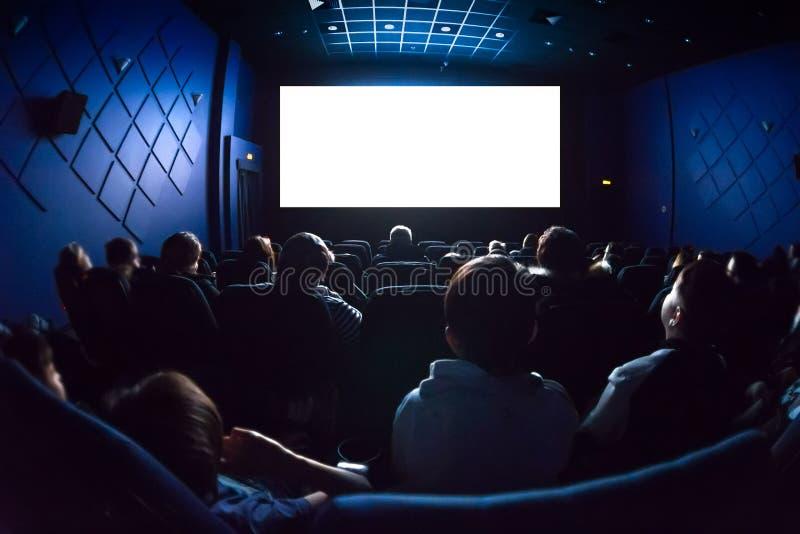 Mensen in de bioskoop die op een film letten Het lege lege witte scherm stock foto