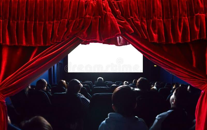 Mensen in de bioskoop die op een film letten Het lege lege witte scherm Rood theatergordijn op de voorgrond stock afbeelding