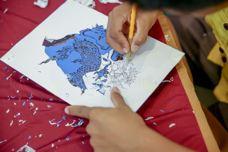 Mensen de handen die gebruiken ambachtmes, Proces die van hand vinyloverdrukplaatjesnaga werken snijden de slang in Thaise mythe, stock foto