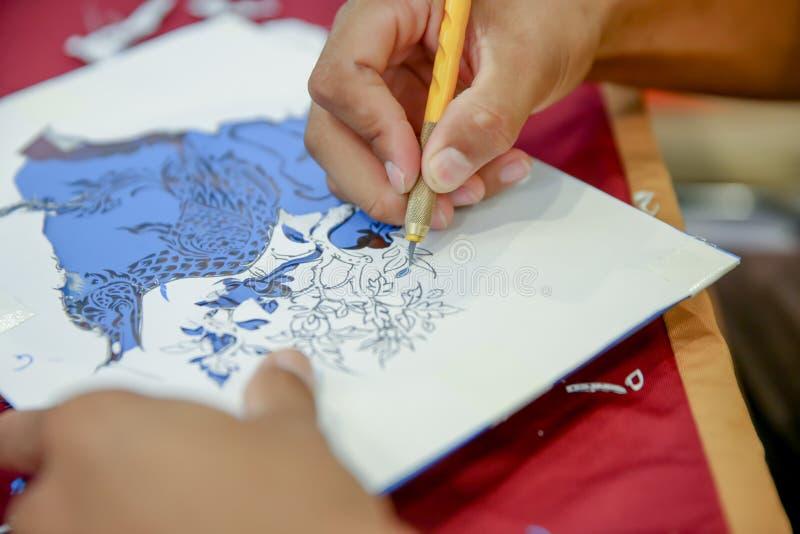 Mensen de handen die gebruiken ambachtmes, Proces die van hand vinyloverdrukplaatjesnaga werken snijden de slang in Thaise mythe, stock fotografie