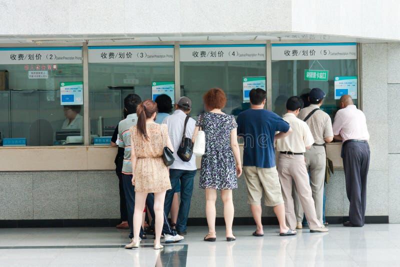 Mensen in de rij bij de vensters van het ziekenhuis stock foto