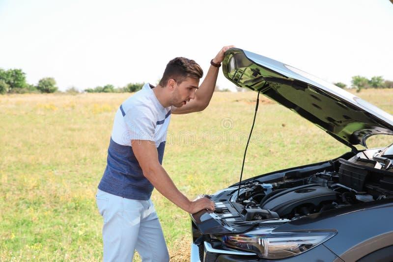 Mensen dichtbij gebroken auto op weg royalty-vrije stock fotografie