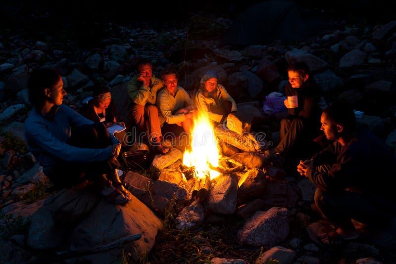 Mensen dichtbij kampvuur in bos royalty-vrije stock foto