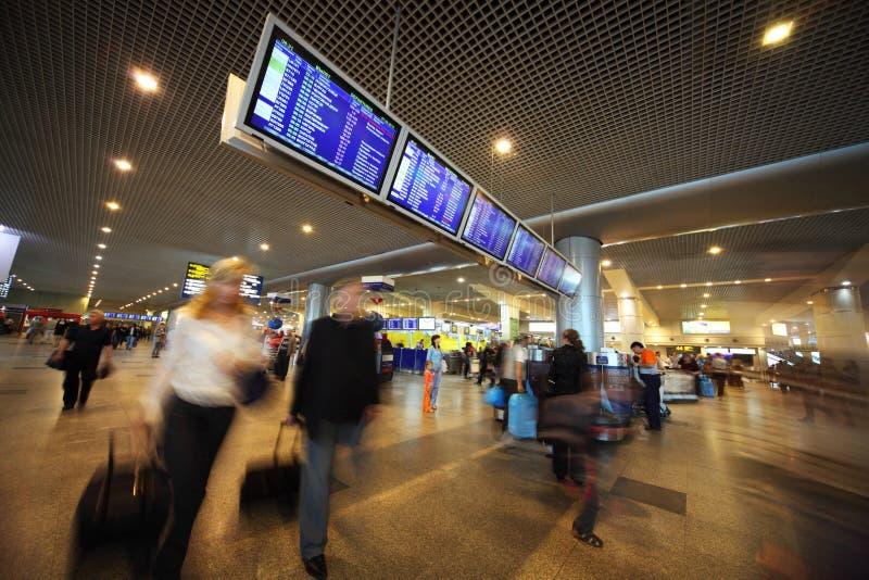 Mensen dichtbij vertoningsraad bij luchthaven stock afbeelding