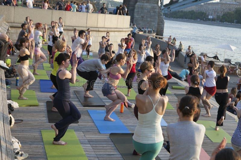Mensen die aan de vrije openbare Yogaklasse in de zomer deelnemen bij stock fotografie