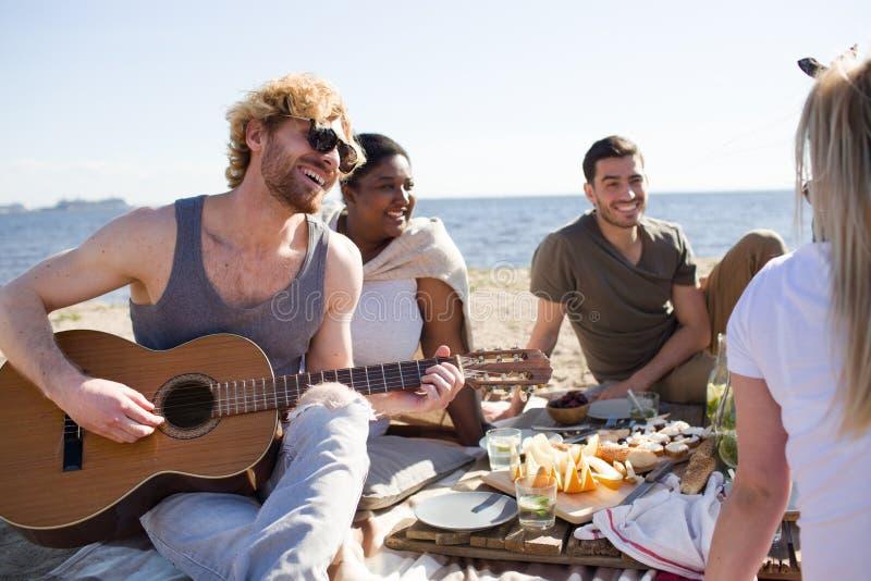 Mensen die aan gitaarmuziek luisteren op strand royalty-vrije stock afbeeldingen