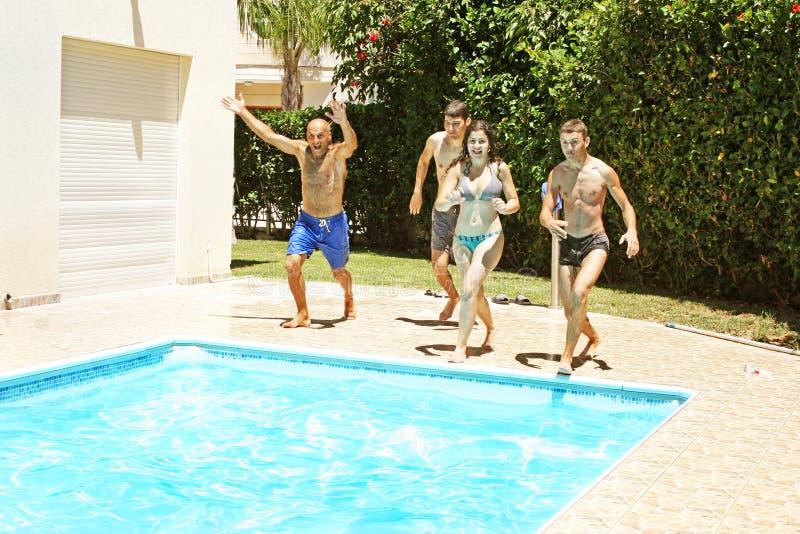 Mensen die aan zwembad springen royalty-vrije stock foto