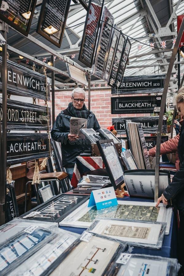 Mensen die affiches en huisdecor bekijken op verkoop bij een box in de Markt van Greenwich, Londen, het UK stock foto's