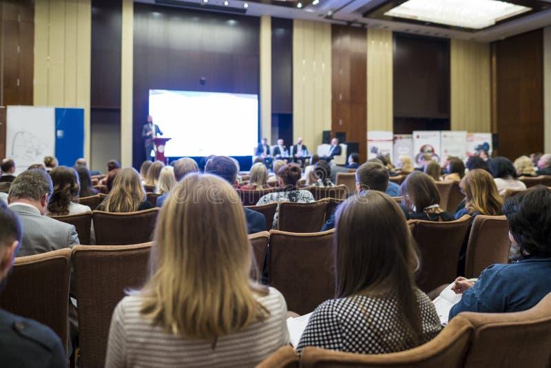 Mensen die Bedrijfsconferentiezitting voor de Gastheer bijwonen royalty-vrije stock foto's