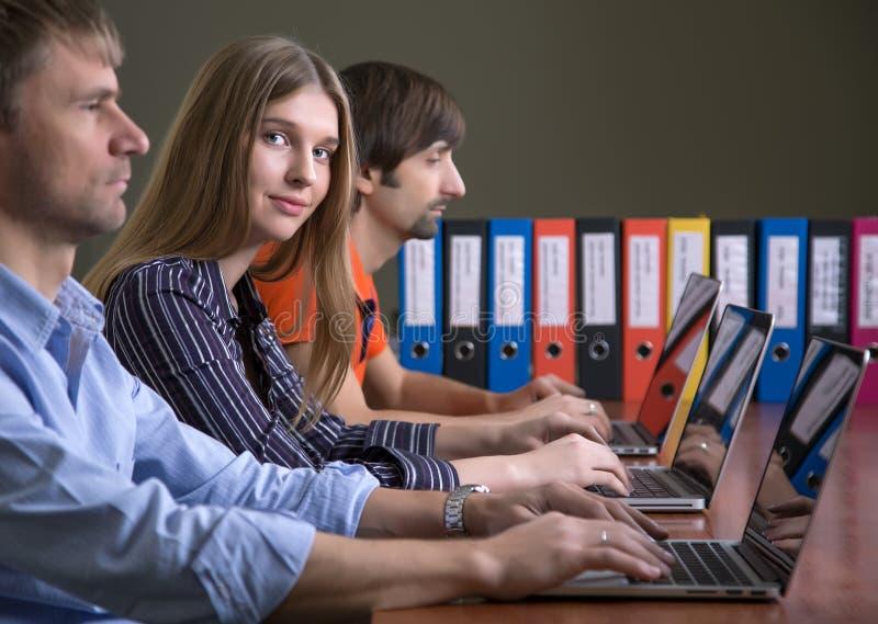 Mensen die bij bureaucomputers werken die in rij mooi wijfje zitten stock afbeeldingen
