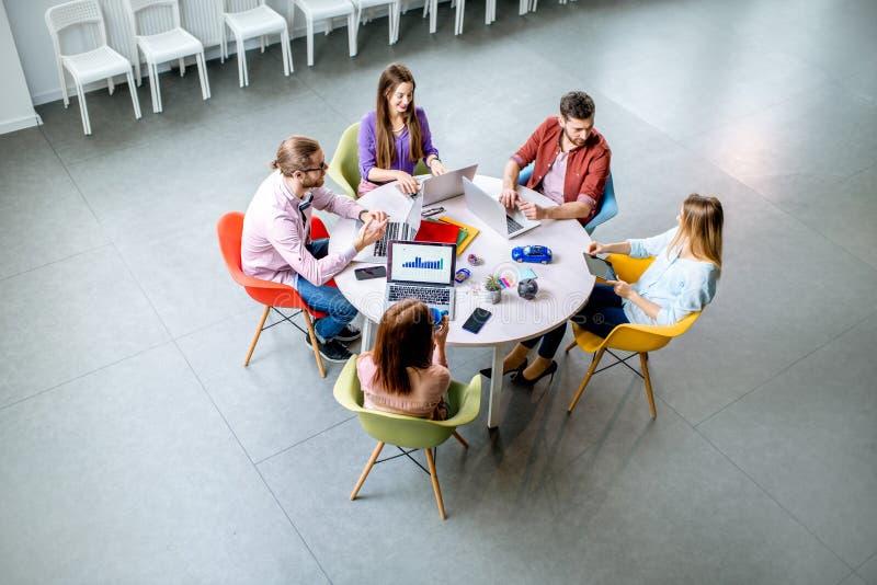Mensen die bij de rondetafel binnen werken stock afbeeldingen