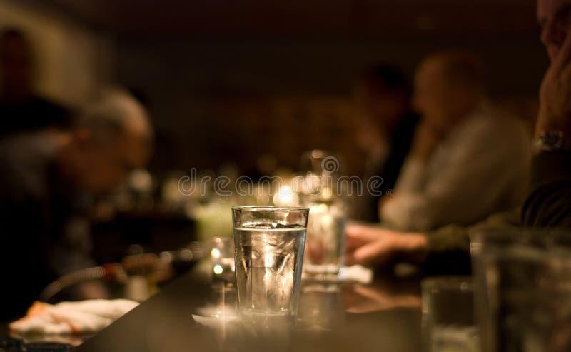 Mensen die bij een staaf drinken stock foto's