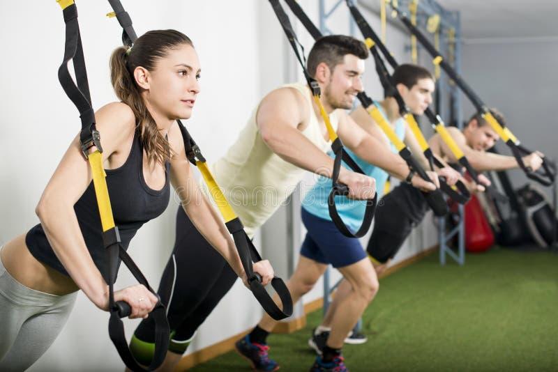 Mensen die bij gymnastiek trx oefeningen doen stock afbeeldingen