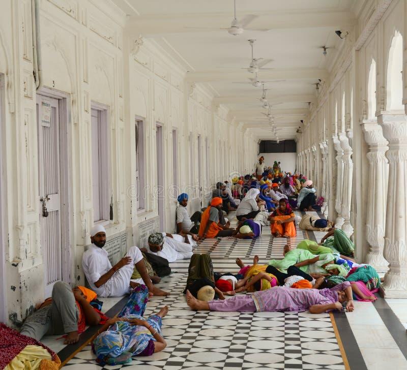 Mensen die bij hal van de Gouden Tempel in Amritsar, India ontspannen stock foto