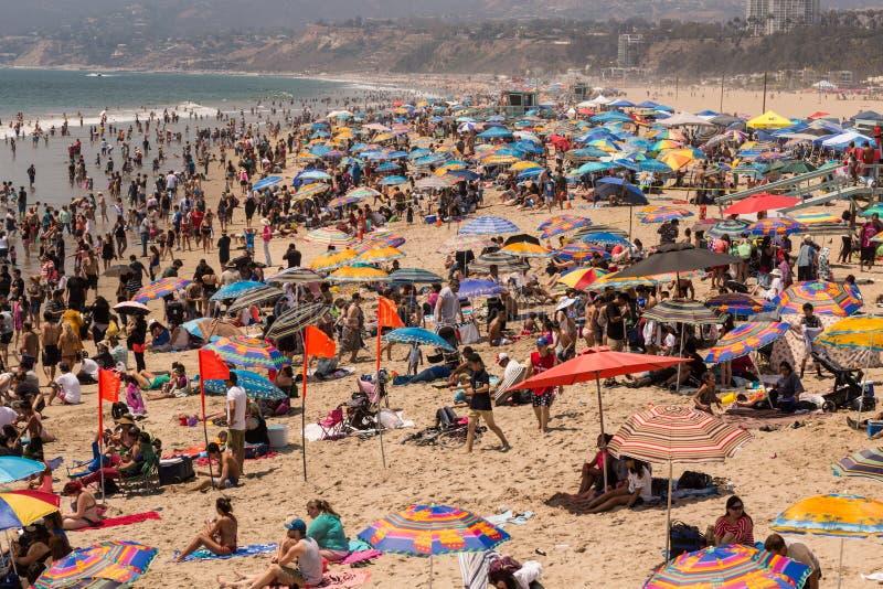 Mensen die bij het strand onder kleurrijke paraplu's spelen royalty-vrije stock foto