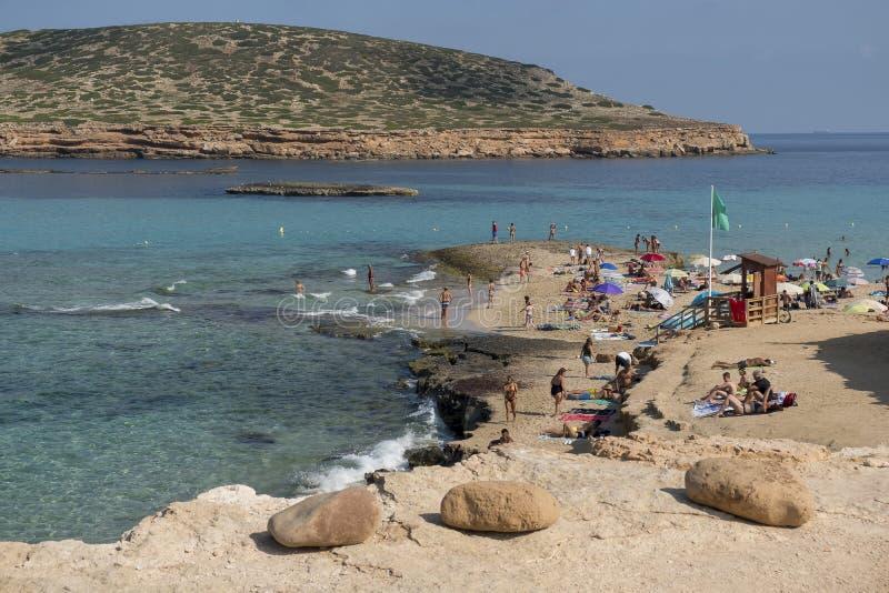 Mensen die bij het strand zonnebaden stock foto's