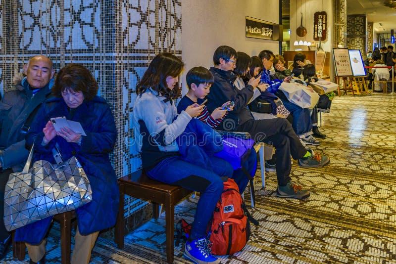 Mensen die bij Restaurant, Osaka - Japan wachten binnen te gaan stock foto's