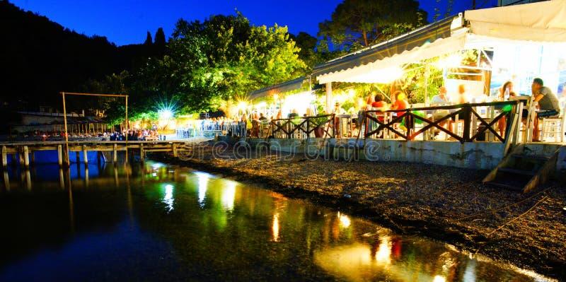 Mensen die bij taverna bij Agnontas-strand, Skopelos, Griekenland dineren stock foto