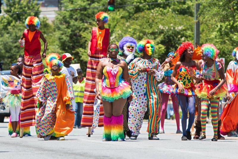 Mensen die Caraïbische de Cultuurparade dragen van Clowncostumes walk in stock afbeeldingen