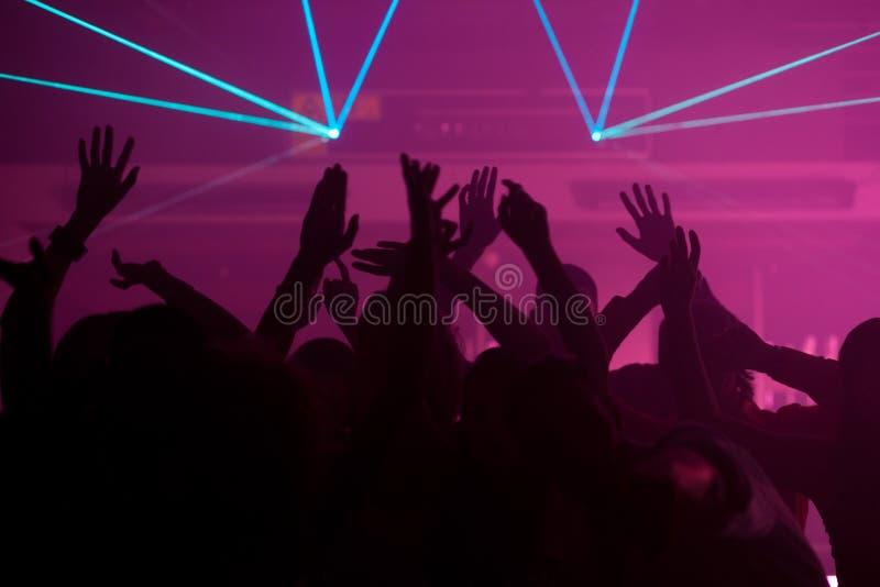 Mensen die in club met lightshow dansen royalty-vrije stock foto's
