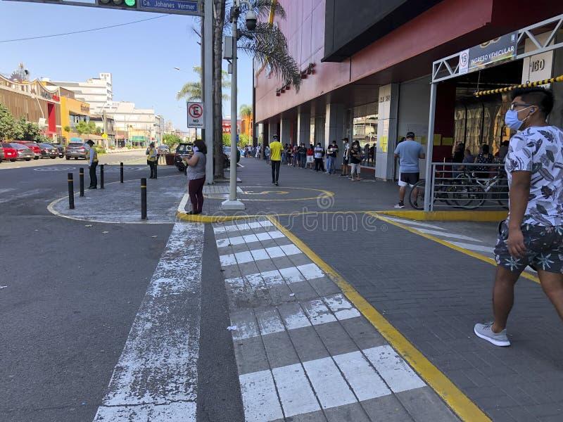 Mensen die de fysieke en sociale afstand in de quarantaine in de stad Lima, Peru, respecteren stock fotografie